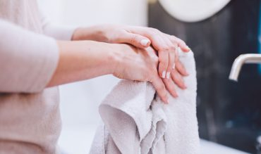 woman-wiping-hands-in-towel-after-washing-them-hyg-22ZGBH4.jpg